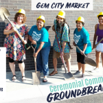 Five Gem City Market Members in plastic hard hats with shovels outside a building. Words on photo tell us it's an invitation to the GCM Community Groundbreaking event on Sept 18th from 4pm to 8pm